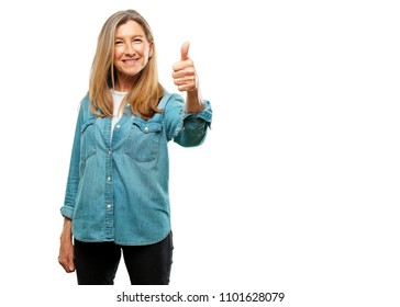 "senior beautiful woman with a satisfied, proud and happy look with thumbs up, signaling OK with one hand, sending a positive, ""alright' message."