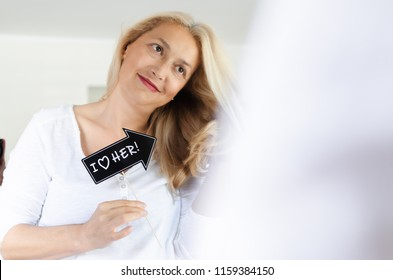 Senior beautiful woman standing in front of mirror and holding photoboth with love massage.