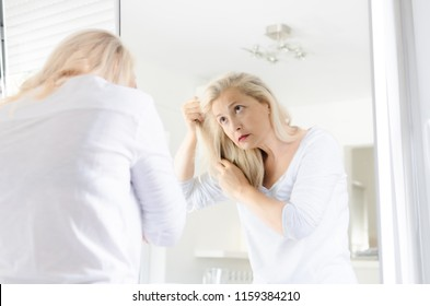 Senior beautiful woman standing in front of mirror looking in her hair.