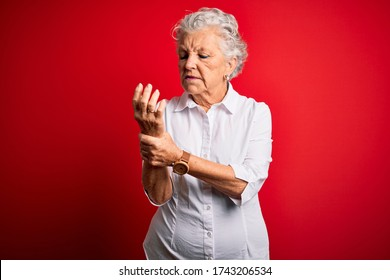 Senior beautiful woman wearing elegant shirt standing over isolated red background Suffering pain on hands and fingers, arthritis inflammation