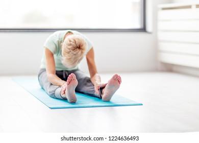 Senior beautivul woman practise joga in room
