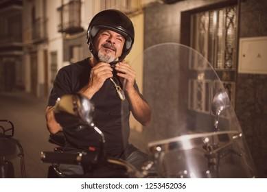 Senior biker adjusting helmet ready for travel on bike