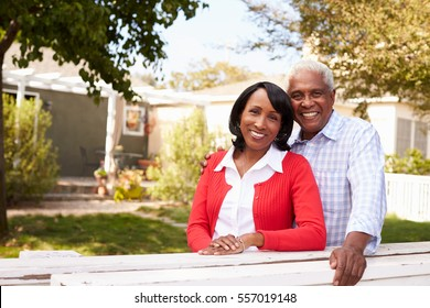 Senior black couple look to camera outside their new house