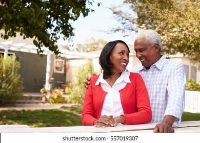 Senior black couple standing outside their new house