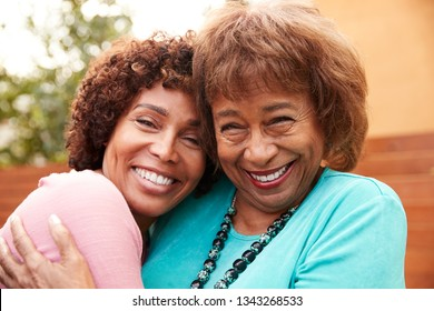 Senior black mum and her middle aged daughter smile to camera embracing, close up
