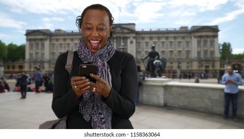 Senior black woman laughing at funny text near Buckingham Palace