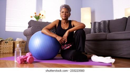 Senior Black woman sitting on floor with exercise equipment