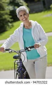 Senior black woman walking her bike through the park