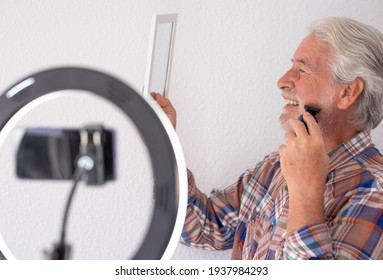 Senior blogger with recording video while shaving . White-haired and beard, white background