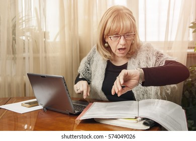 Senior blond woman forgot the time, late for her deadline, covered with documents and unfinished work