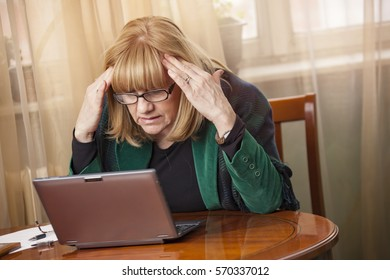 Senior blond woman overworked and stressed out, looking at her laptop with worry