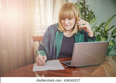 Senior blonde business woman having a professional call, writing down important notes