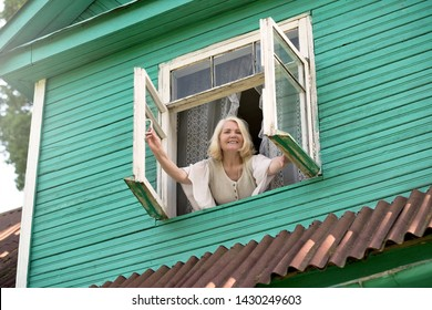 Senior blonde woman opening window inthe morning morning waking up. Active morning at the country side or village.