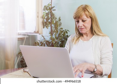 Senior blonde woman using a computer at her home, browsing internet and utilizing modern technologies