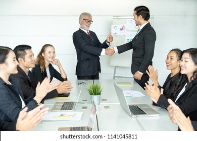 Senior Boss or CEO promoting young subordinate. Two businessmen handshaking, congratulating on promotion. Celebration of promotional event.