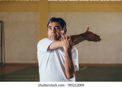 Senior Brazilian or Latin man wearing white blank shirt doing exercises at sports gym