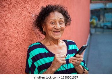 Senior brazillian reading a message on smartphone