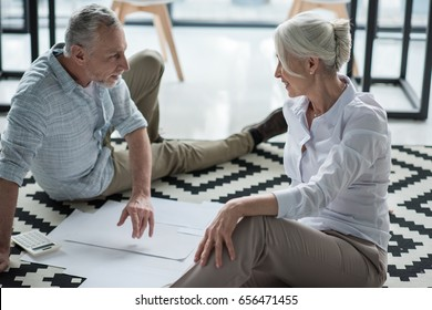 Senior business colleagues converse at office