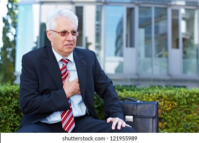 Senior business man with aching heart holding his chest