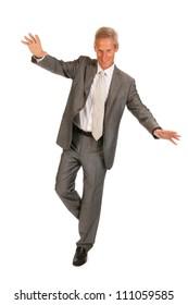 Senior business man balancing at one leg isolated over white background