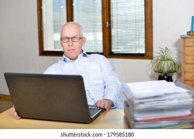 Senior business man in blue shirt at the office and computer