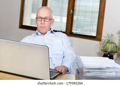 Senior business man in blue shirt at the office