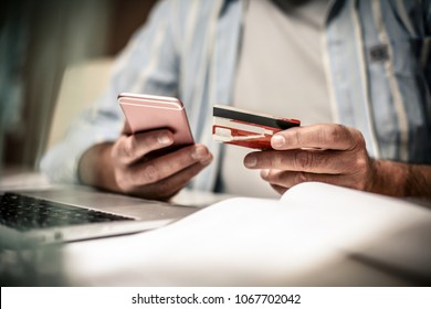 Senior business man checking his finance on credit card. Close up. Focus is on hand.