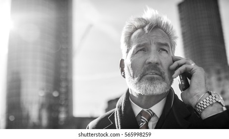 Senior business man in the city talking on his phone