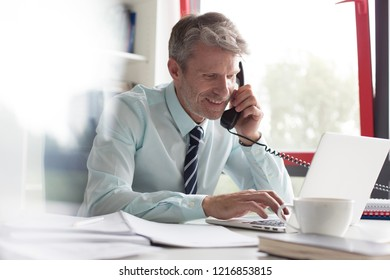 Senior business man in his office making a phone call and typing notes whilst looking very happy
