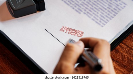 senior business man male hand putting or signing signature in the certificate contract after approve stamp on loan document agreement lawyer hand concept