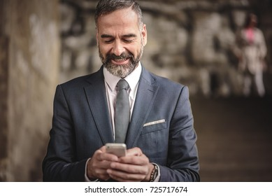 Senior business man receiving a happy message on his cell phone, outdoor urban area