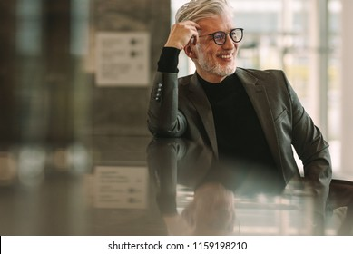 Senior business man relaxing at cafe. Mature man sitting at coffee shop counter and looking away smiling.