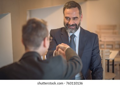 Senior business man shaking hands with a junior employee, congratulating him on passing the job interview
