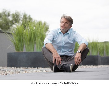 Senior business man with shoes off and legs cross performing looking sad and depressed from working too hard. He seems to be stressed and thinking about his personal life.