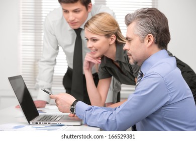 Senior  business man showing something on laptop. Sitting together with group of business people in modern office