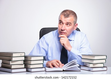 senior business man sitting at his desk full of books and looking pensively to a side, with his hand on his chin. on gray background