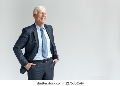 Senior business man studio standing isolated on gray wall hands in pockets looking aside laughing happy