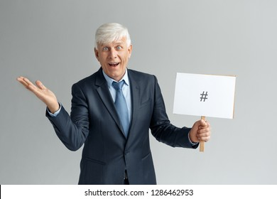 Senior business man studio standing isolated on gray wall holding white board with pound sign looking camera smiling excited