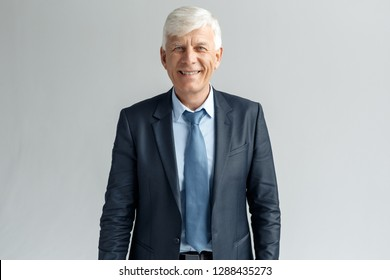 Senior business man studio standing isolated on gray wall looking camera smiling cheerful