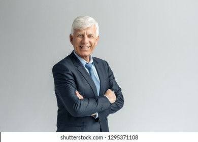 Senior business man studio standing isolated on gray wall crossed arms looking camera smiling confident