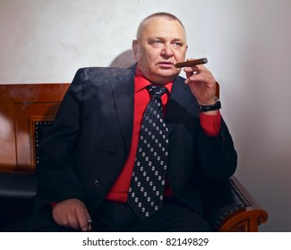 Senior business man wearing red shirt, black coat and tie sitting on leather sofa and smoking cigar indoor