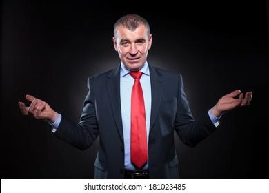 senior business man welcoming you , on dark studio background