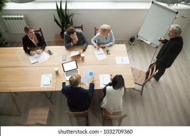 Senior business mentor coaching executive managers team at corporate group meeting in conference room, company ceo giving presentation to partners discussing new strategic plan, top view from above