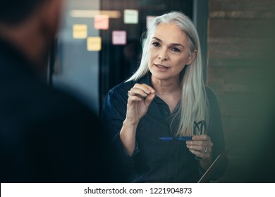 Senior business woman explaining business matters to her team in a meeting . Mature female manager advising her colleagues in meeting.