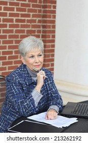 Senior Business Woman Happy and Confident Mature Elderly Senior Citizen Holding a Pen While Thinking and Looking to the Side While Sitting at a Desk