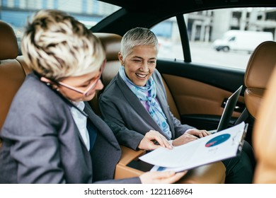 Senior business woman and her assistant sitting in limousine talking and working.
