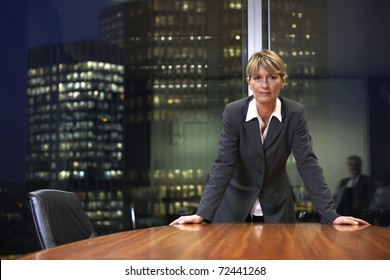 Senior Business woman leaning on table in boardroom looking at camera
