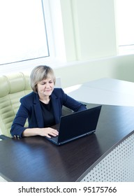 senior business woman with notebook in office interior