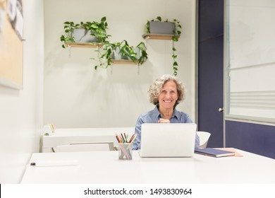 Senior business woman on laptop computer as typist or manager