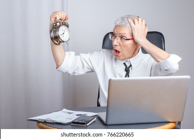 Senior business woman realizing what time it is, late for her deadline